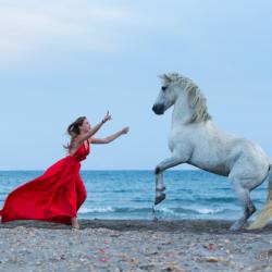 Dziewczyna w czerwonej sukni z koniem na plaży w Camargue