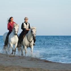 Amazonki jadące konno nad morzem w Camargue