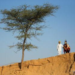 Hindus z klaczą Marwari na piasku na tle nieba