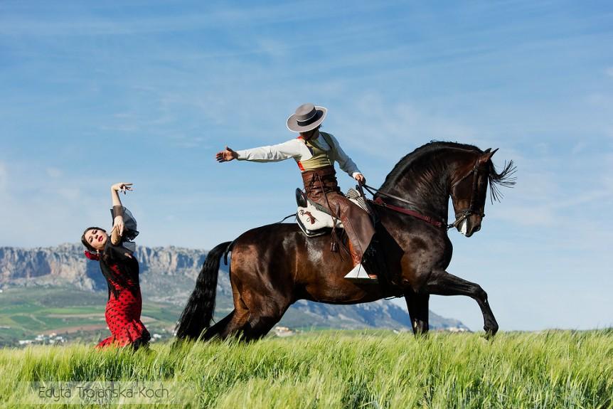 Jeździec na ogierze andaluzyjskim tańczący z tancerką flamenco w górach Andaluzji