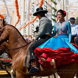 Jeździec z dziewczyną w stroju flamenco podczas feria de Sevilla