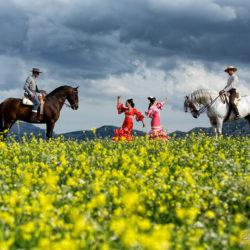 Tancerki flamenco i jeźdźcy doma vaquera na tle gór