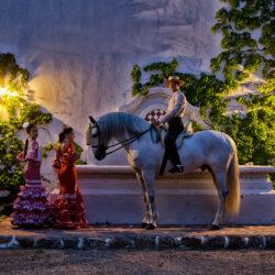 Tancerki flamenco i jeździec doma vaquera w patio wieczorem