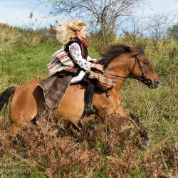 Blondynka galopująca jesienią na hucule w stroju huculskim