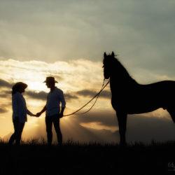 Kobieta i mężczyzna z andaluzem w górach o zachodzie słońca