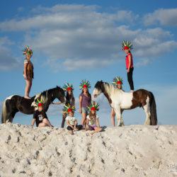 Dzieci z tinkerami w pióropuszach na białych piaskach