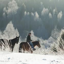 Jeździec z luzakiem zimą w górach
