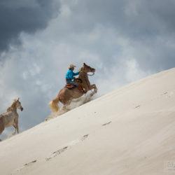 Jeździec w stylu western galopujący pod górę po białym piasku