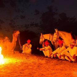 Hindusi z końmi i wielbłądem przy ognisku