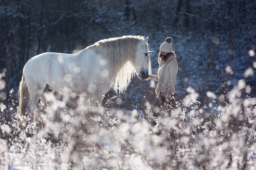 Young woman standing with her unicorn in winter scenery