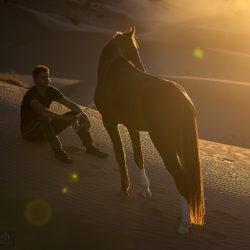 Berber z koniem na wydmach na pustyni w Maroku