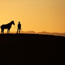 Berber z koniem o zachodzie na pustyni
